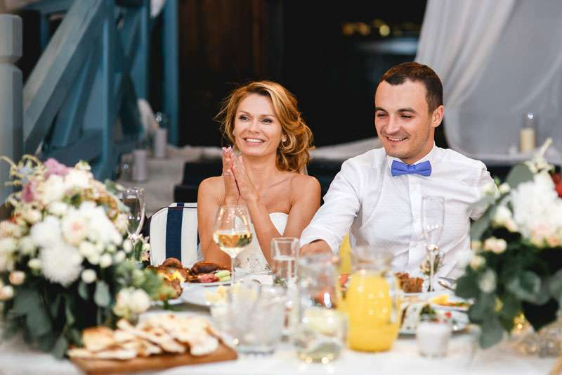 Bride and Groom Smiling at Dinner Table